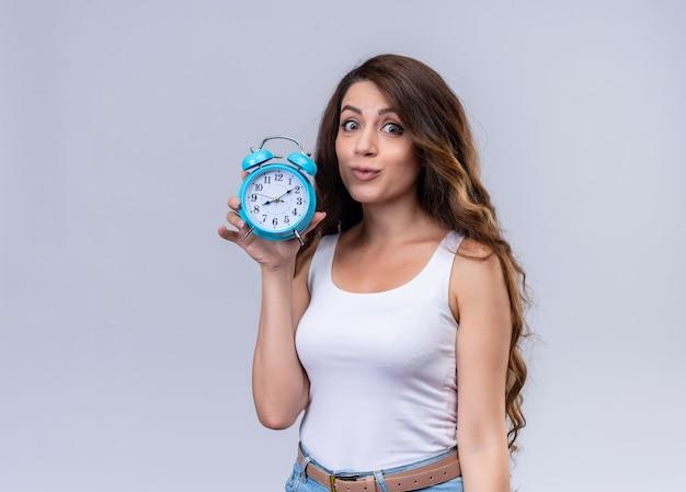 Впечатленная молодая красивая девушка держит будильник с копией пространства