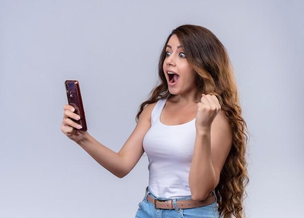 Впечатленная молодая красивая девушка держит мобильный телефон, глядя на него с поднятым кулаком