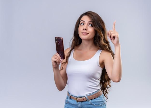 Впечатленная молодая красивая девушка, держащая мобильный телефон, поднимая палец с копией пространства