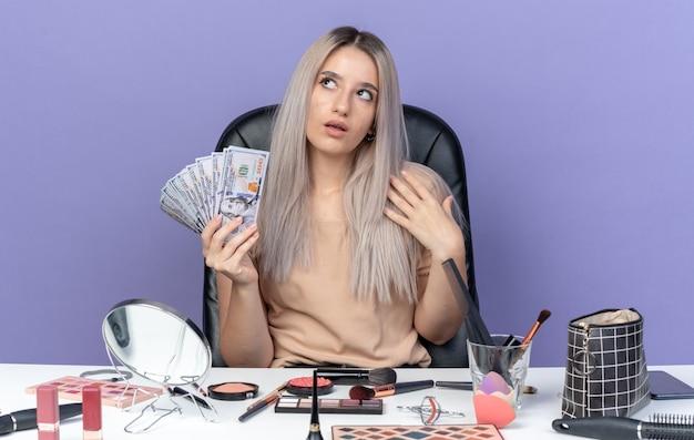 Впечатленная молодая красивая девушка сидит за столом с инструментами для макияжа и держит деньги, изолированные на синей стене