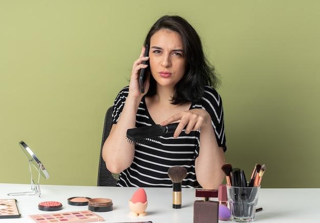 Впечатленная молодая красивая девушка сидит за столом с инструментами для макияжа, держа расческу, говорит по телефону, изолированному на оливково-зеленой стене