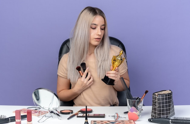 Впечатленная молодая красивая девушка сидит за столом с инструментами для макияжа, держа чашку победителя с кистью для макияжа, изолированной на синей стене