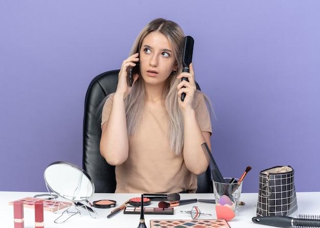 Впечатленная молодая красивая девушка сидит за столом с инструментами для макияжа, разговаривает по телефону, расчесывая волосы, изолированные на синей стене