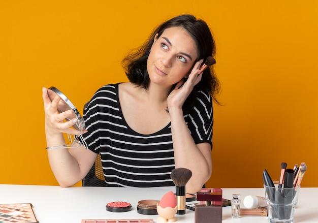 La giovane bella ragazza impressionata si siede alla tavola con gli strumenti di trucco che tengono lo specchio con la spazzola della polvere isolata sulla parete arancio