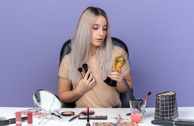 La giovane bella ragazza impressionata si siede alla tavola con gli strumenti di trucco che tengono la tazza del vincitore con la spazzola di trucco isolata sulla parete blu