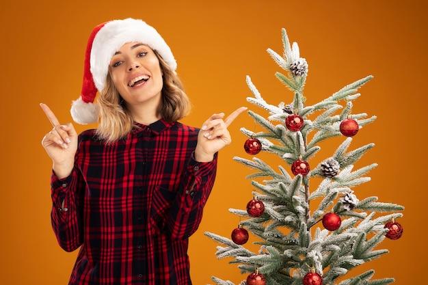 オレンジ色の背景で隔離の異なる側にクリスマスの帽子のポイントを身に着けているクリスマスツリーの近くに立っている感動の若い美しい少女
