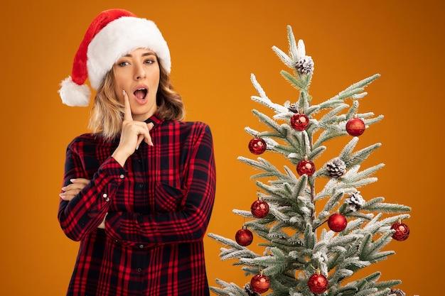 Impressionata giovane bella ragazza in piedi vicino all'albero di natale con il cappello di natale mettendo il dito sulla guancia isolato su sfondo arancione