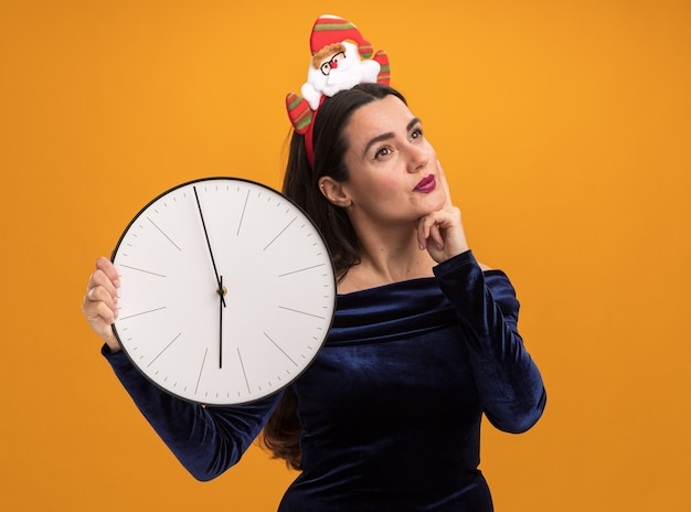 Впечатленная молодая красивая девушка в синем платье и рождественском обруче для волос держит настенные часы, положив руку на щеку, изолированную на оранжевой стене