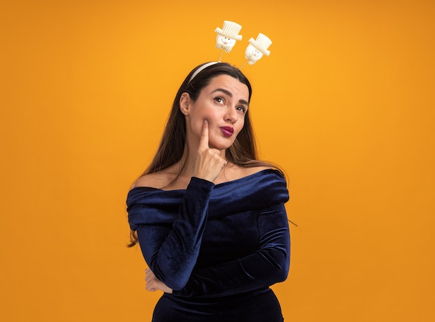 Impressed young beautiful girl wearing blue dress and christmas hair hoop putting finger on cheek isolated on orange background