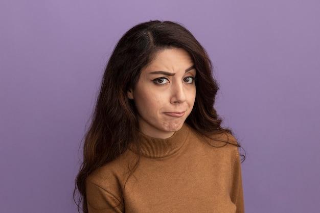 Impressionato giovane bella ragazza che indossa un maglione dolcevita marrone isolato sulla parete viola