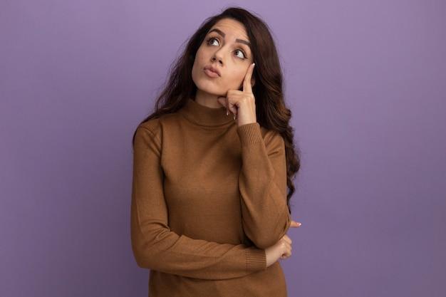 보라색 벽에 고립 된 뺨에 손가락을 넣어 갈색 터틀넥 스웨터를 입고 감동 젊은 아름 다운 소녀