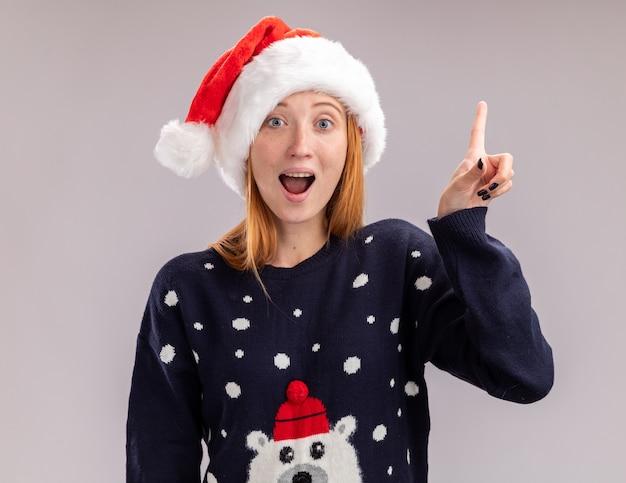 Впечатленная молодая красивая девушка в рождественской шляпе указывает вверх на белой стене