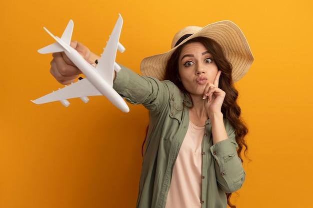 オリーブ グリーンの t シャツと帽子を着て、黄色の壁に分離された頬に指を置くカメラでおもちゃの飛行機を差し出す帽子をかぶった印象的な若い美しい女の子
