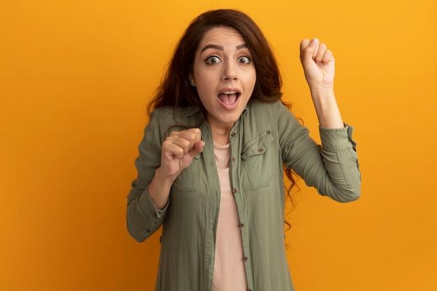 Impressionata giovane bella ragazza che indossa una maglietta verde oliva che tiene i pugni isolati sul muro giallo