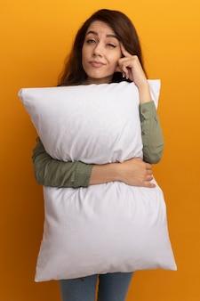 Впечатленная молодая красивая девушка в оливково-зеленой футболке обняла подушку, положив палец на висок, изолированное на желтой стене