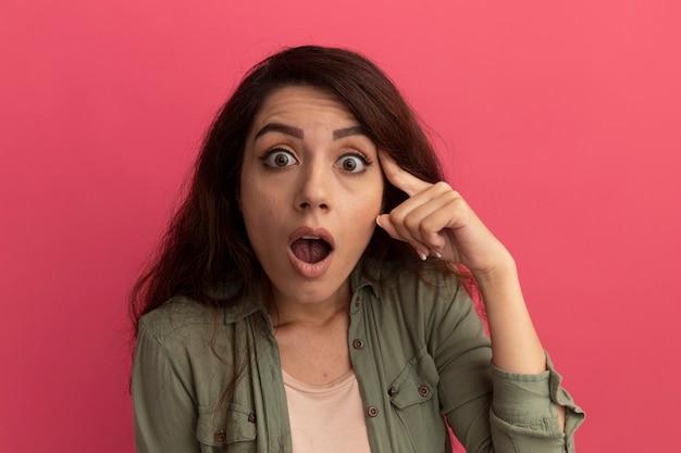 Giovane bella ragazza colpita che indossa la maglietta verde oliva che mette il dito sul tempio isolato sulla parete rosa