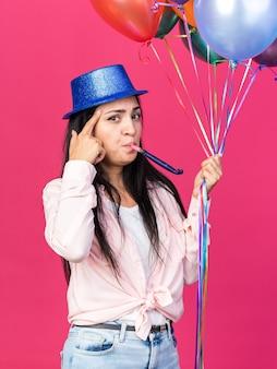 Впечатленная молодая красивая девушка в шляпе для вечеринки, держащая воздушные шары, дует партийный свисток, положив палец на храм