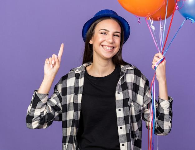 青い壁に隔離された上に風船ポイントを保持しているパーティーハットを身に着けている感動の若い美しい少女