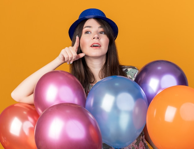 Impressed young beautiful girl wearing party hat standing behind balloons points isolated on orange wall