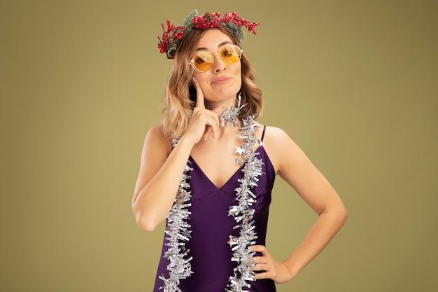 紫色のドレスとメガネを身に着けている印象的な若い美しい少女は、オリーブグリーンの背景で隔離の頬に指を置いて花輪と花輪を首にかけます。