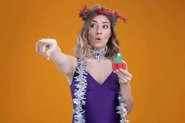 茶色の背景で隔離の側にクリスマスのおもちゃのポイントを保持している首に花輪と紫色のドレスと花輪を身に着けている感動の若い美しい少女