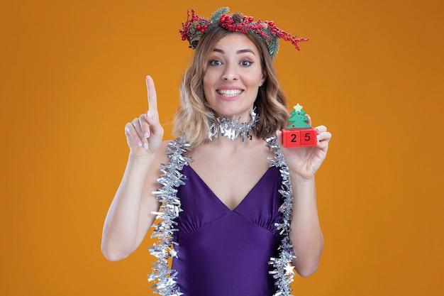 茶色の背景で隔離のクリスマスのおもちゃのポイントを保持している首に花輪と紫色のドレスと花輪を身に着けている感動の若い美しい少女