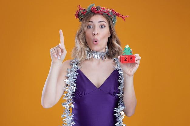 Впечатленная молодая красивая девушка в фиолетовом платье и венке с гирляндой на шее, держащая рождественскую игрушку, указывает вверх на коричневом фоне