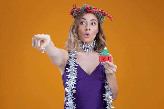 Impressed young beautiful girl wearing purple dress and wreath with garland on neck holding christmas toy points at side isolated on brown background