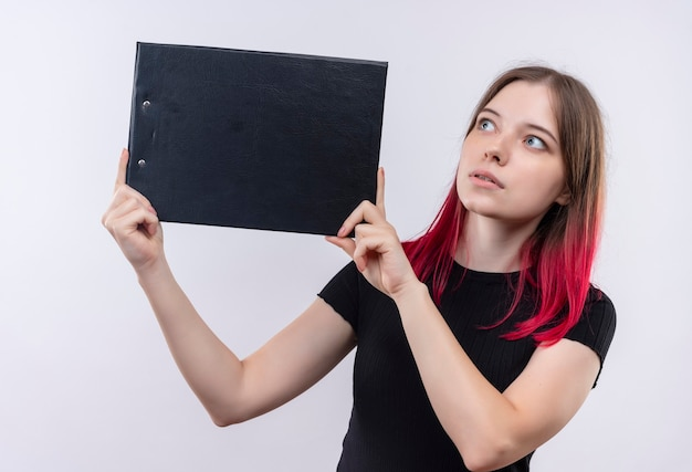 Impressed young beautiful woman wearing black t-shirt holding clipboard on isolated white wall