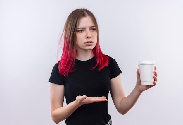 La giovane bella donna impressionata che porta la maglietta nera indica la tazza di caffè in sua mano sulla parete bianca isolata