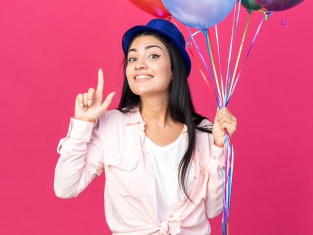 ピンクの壁に隔離された上に風船ポイントを保持しているパーティーハットを身に着けている感動若い美しい女性