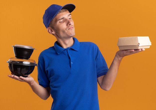 Impressed young blonde delivery boy holds food containers and looks at food package