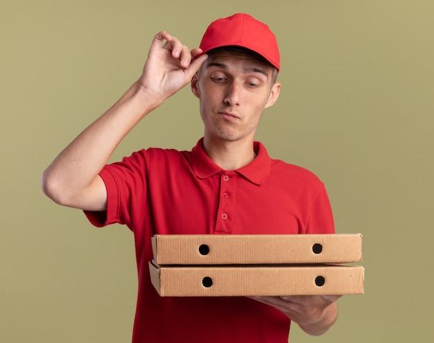 Впечатленный молодой блондин посыльный кладет руку на кепку, держа и глядя на коробки для пиццы, изолированные на оливково-зеленой стене с копией пространства