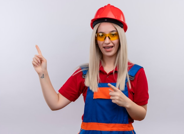 Impressed young blonde engineer builder girl in uniform in dental braces wearing safety glasses pointing at left side on isolated white space