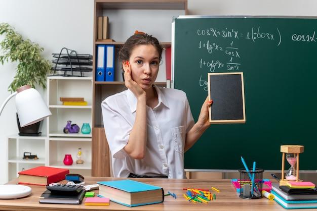 Impressionato giovane insegnante di matematica femminile bionda seduto alla scrivania con strumenti scolastici che tengono mini lavagna tenendo la mano sul viso guardando la fotocamera in aula
