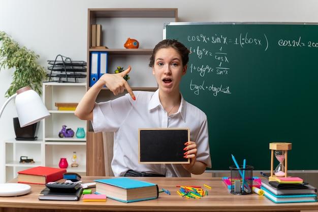 Impressionato giovane insegnante di matematica femminile bionda seduto alla scrivania con strumenti di scuola che tengono e puntano alla mini lavagna guardando la fotocamera in aula