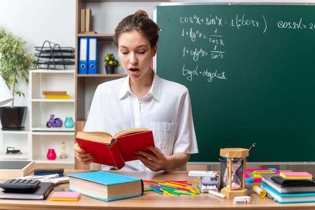 Impressionato giovane insegnante di matematica femminile bionda seduta alla scrivania con strumenti di scuola che legge un libro in classe