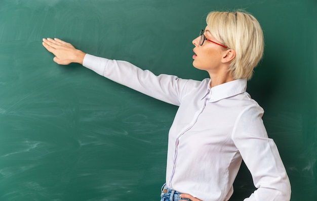 Impressed young blonde female teacher wearing glasses in classroom standing in profile view in front of chalkboard looking at and pointing at chalkboard with hand keeping another hand on waist