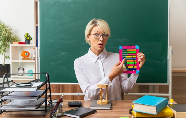 Impressed young blonde female teacher wearing glasses sitting at desk with school supplies in classroom showing abacus pointing at it