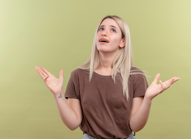 Impressed young blonde girl in dental braces looking up on isolated green space