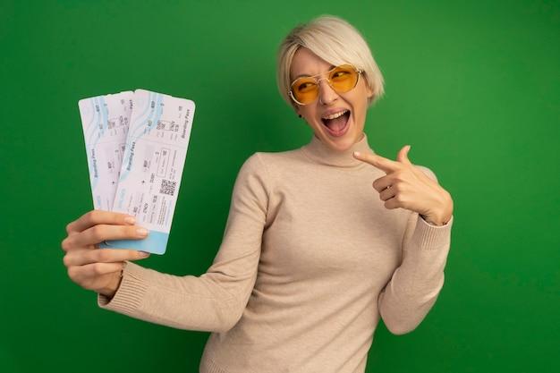 緑の壁に隔離された飛行機のチケットを持って指さしている印象的な若いブロンドの女の子