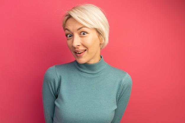 Giovane ragazza bionda impressionata che sembra isolata sulla parete rosa con lo spazio della copia