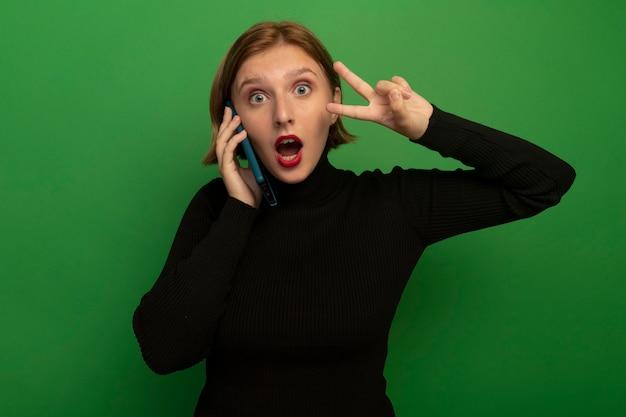 緑の壁に分離された平和のサインをやって電話で話している印象的な若いブロンドの女の子