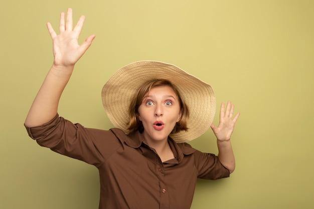手を上げてビーチ帽子をかぶって感動した若いブロンドの女の子