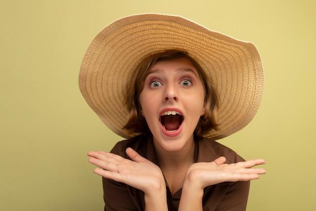 빈 손을 보여주는 해변 모자를 쓰고 감동 어린 금발 소녀