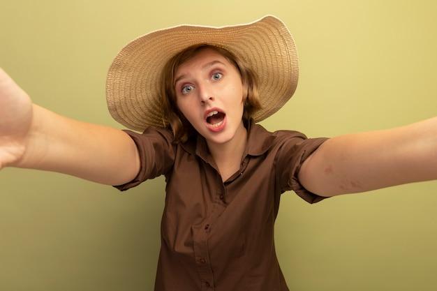 Colpita la giovane ragazza bionda che indossa il cappello da spiaggia che allunga le mani