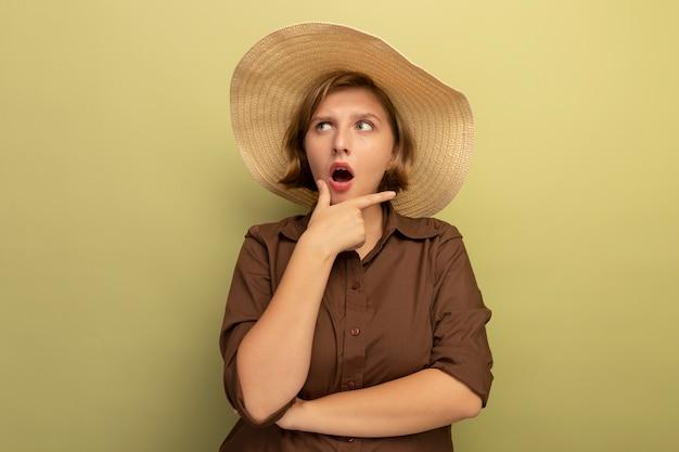 Colpito la giovane ragazza bionda che indossa il cappello da spiaggia che tocca il mento guardando il lato