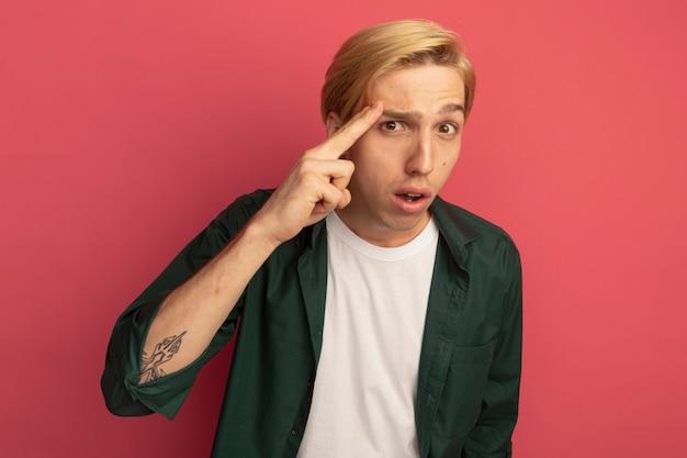 Giovane ragazzo biondo impressionato che indossa la maglietta verde che mette il dito sulla tempia