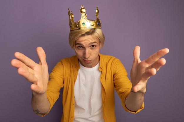 Giovane ragazzo biondo impressionato che indossa la maglietta gialla e la corona che tengono le mani alla macchina fotografica isolata sulla porpora