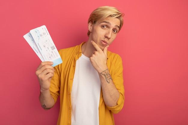 노란색 티셔츠를 입은 젊은 금발의 남자가 티켓을 들고 턱을 잡았습니다.